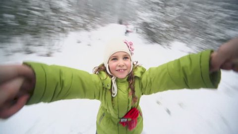 Hand holds little girl which flies above snow at background of winter forest