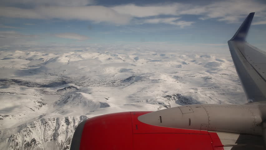 Airplane window view mountain winter landscape