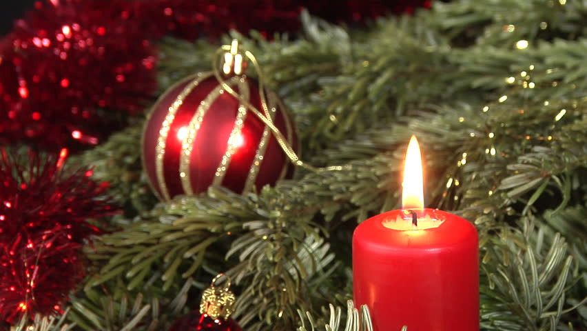 Elaborate christmas decoration with glass balls, christmas greens and candles. Camera locked down