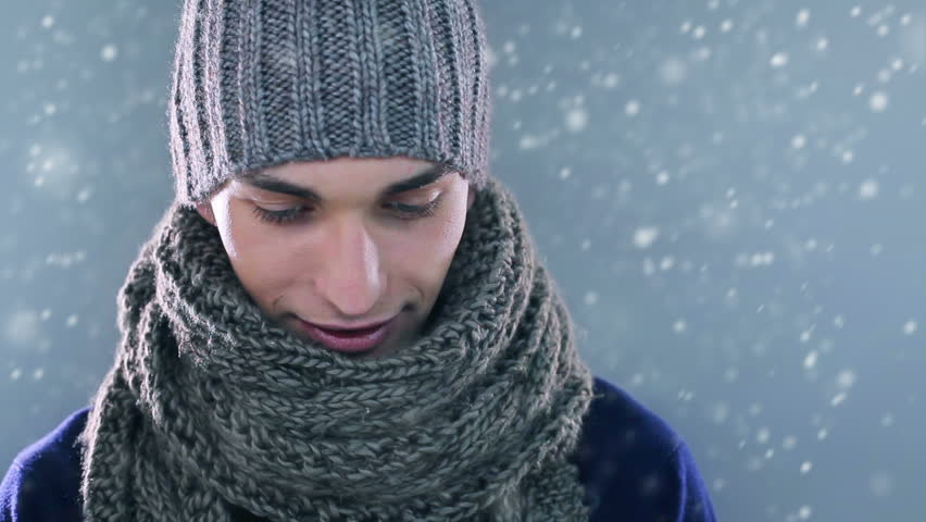 Handsome young man wearing a knit hat and a scarf and smiling.