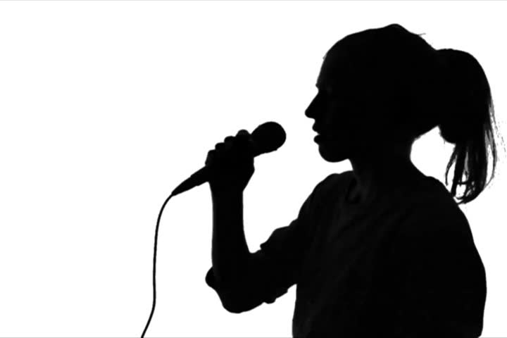 Young adult woman holds microphone and sings  against green screen chroma background. Back-lit silhouette. Close-up shot.
