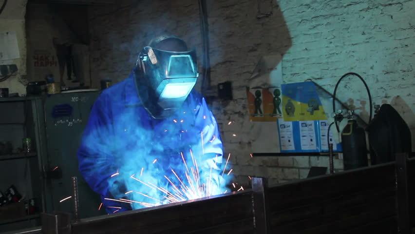 Male wearing uniform welds with welding machine torch