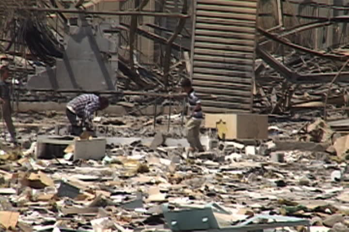 BAGHDAD, IRAQ - JULY 26, 2003: Two people picking through building rubble, camera pulls back to show city block filled with rubble and debris.