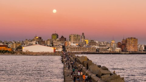 MONTEVIDEO - MAR 26: Timelpase view of Montevideo city with fishermen moving in the foreground ant the moon over the city on 26 March 2013 in Montevideo, Uruguay