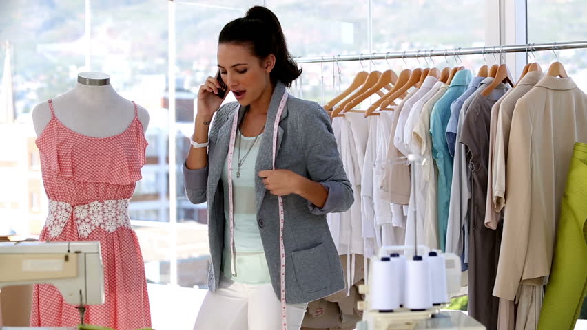 Attractive fashion designer on the phone working on a dress | Shutterstock HD Video #4110193