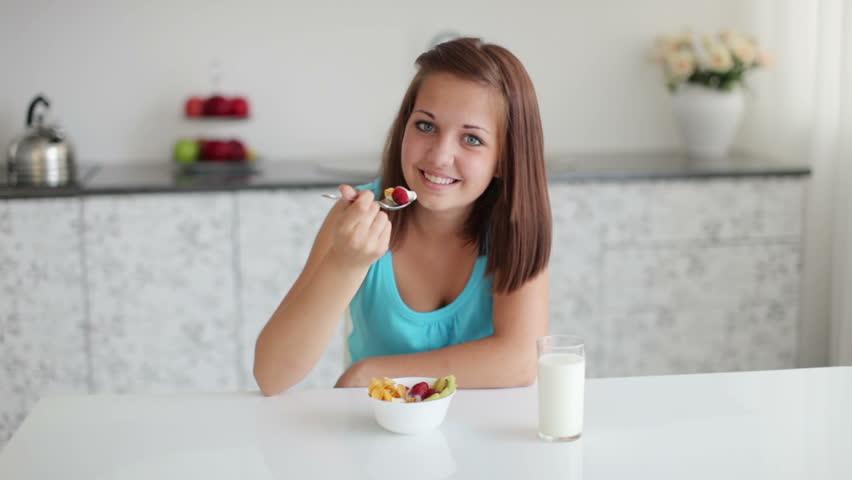 Sweet girl eating yogurt with fruits