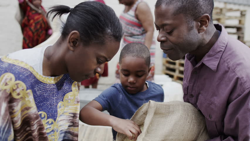 A mother and father from a poor African community work together with their young son, measuring out quantities of rice or grain. In slow motion.