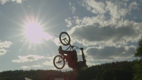 BMX Bike Rider does a Backfli. silhouette with flare.