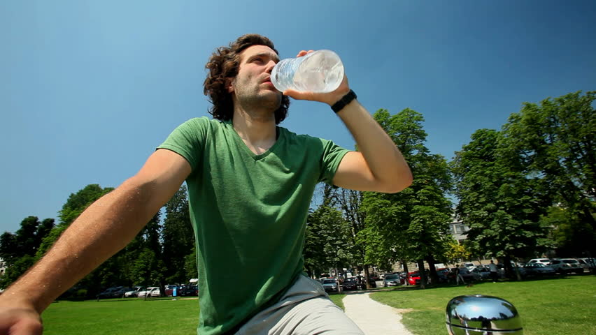 Young man drinking bottle of water on bike in park in summer