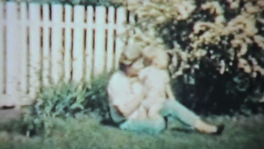 A cute little boy has fun playing with his beloved Grandmother in the backyard in the summer of 1963.