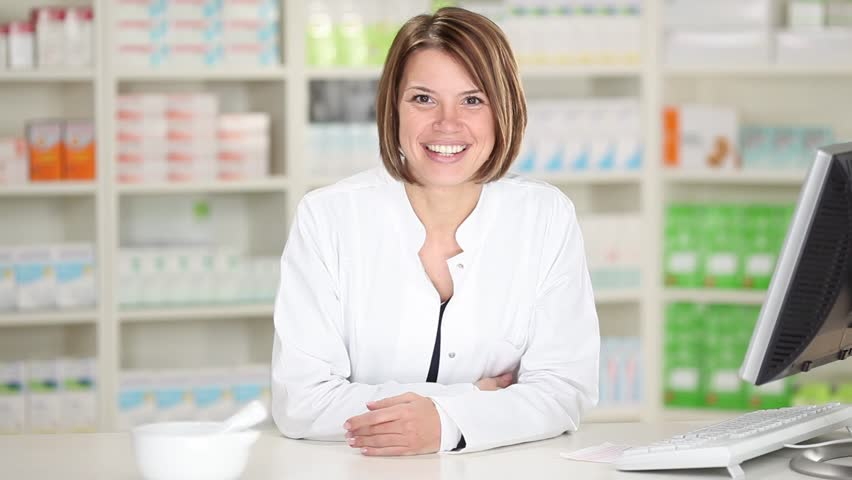 Happy cheerful pharmacist chemist woman leaning on counter in pharmacy drugstore