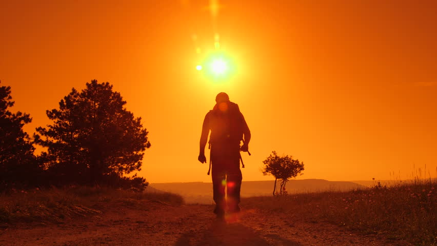 Hiker on the trail at sunset, lifting hands | Shutterstock HD Video #4192663