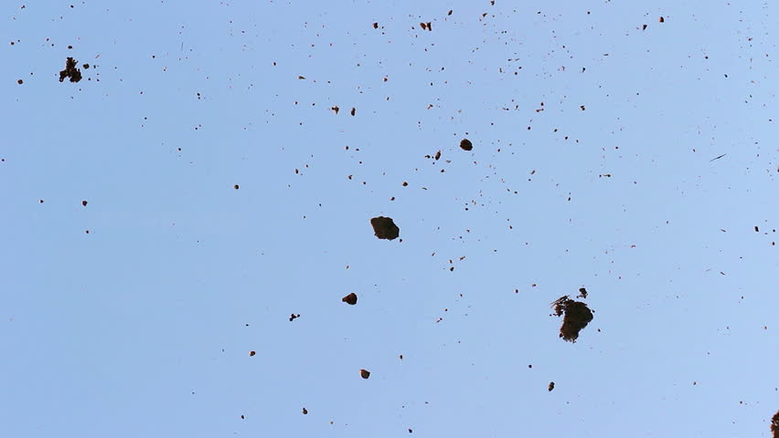 red glowing ash drops on window, moved around by storm, filmed from below against blue sky