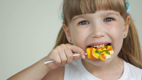 Girl biting a lollipop and smiling