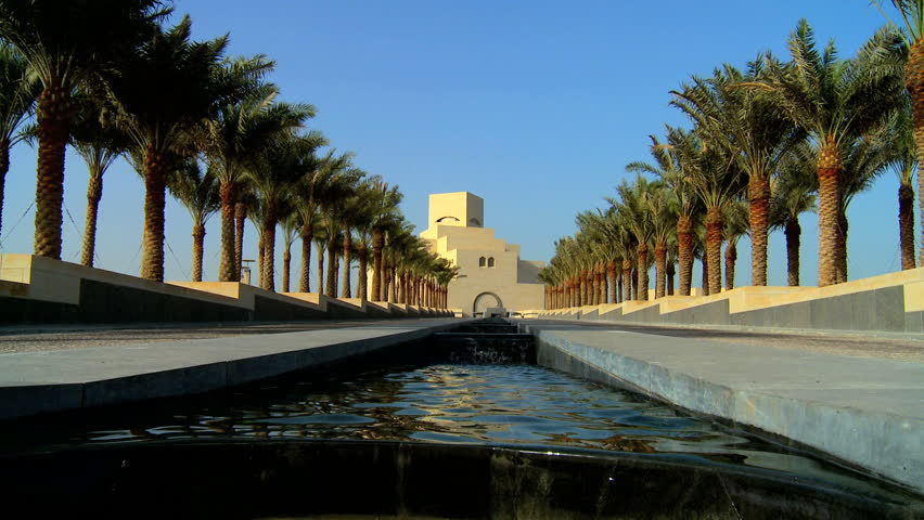 Channel of clear running water in avenue of palm trees in front of Islamic Museum of Art, Doha, Qatar