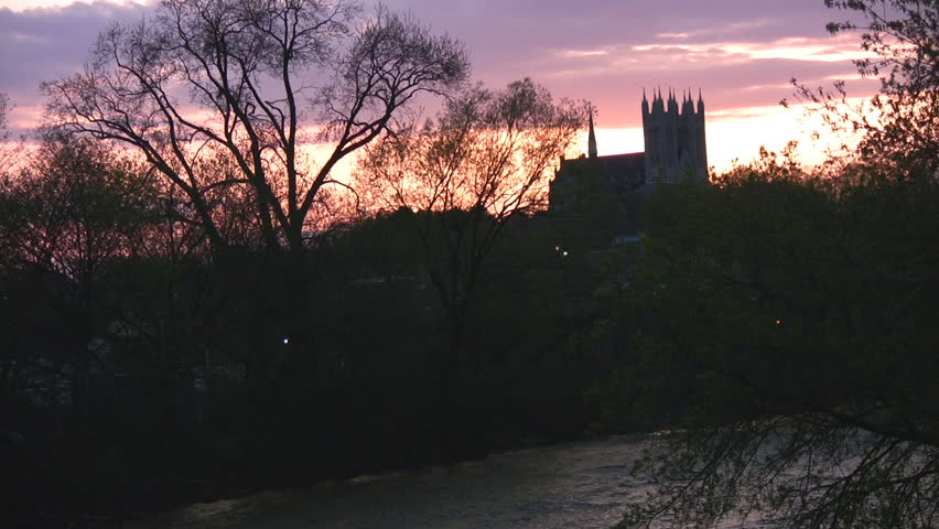 A church in the distance, highlighted by a sunset full of purples, oranges, and pinks, with a river below.  Guelph, Ontario, Canada