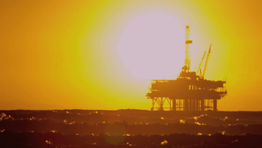 Oil rig drilling for fuel in silhouette on coastal platform at sunset shot on RED EPIC
