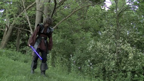 Two men duel with futuristic glowing blue laser swords.  Real time with normal shutter speed on grassland in front of woods.  Hand held camera.