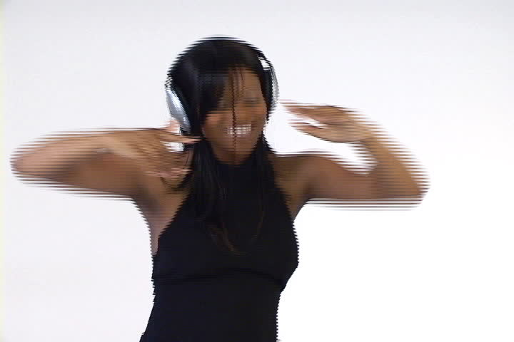 A young African American woman with headphones on dances to the beat.