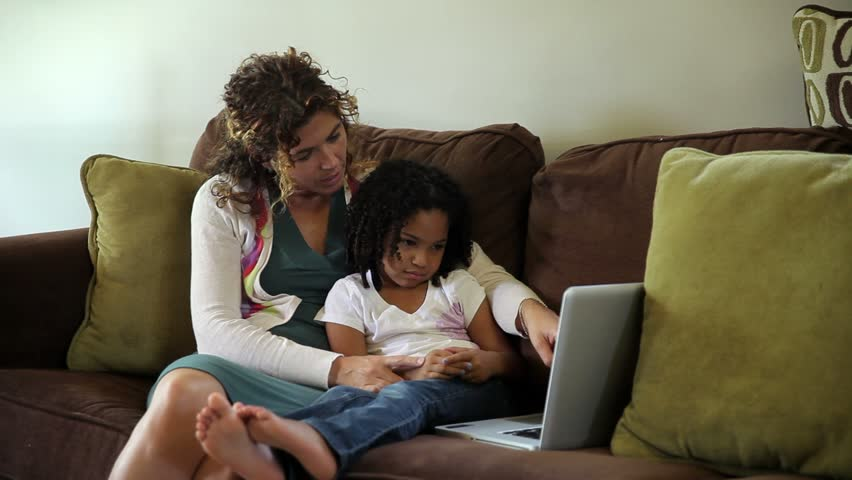 Tired biracial little girl with ethnic woman on brown couch watching laptop video on computer. Could be used for family, mother daughter, watching movie, bi-racial, multi ethnic, african american...