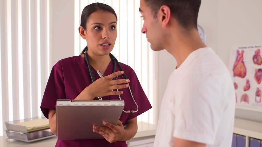 Mexican nurse talking with male patient