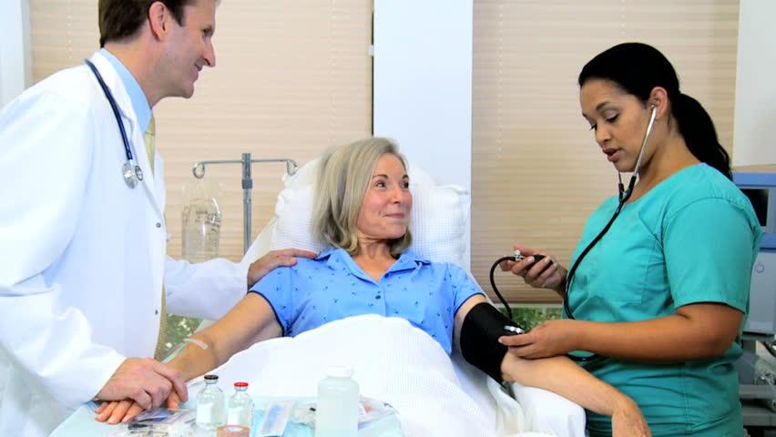 Hospital doctor attending nurse taking the blood pressure of a senior Caucasian female on ward #4312523