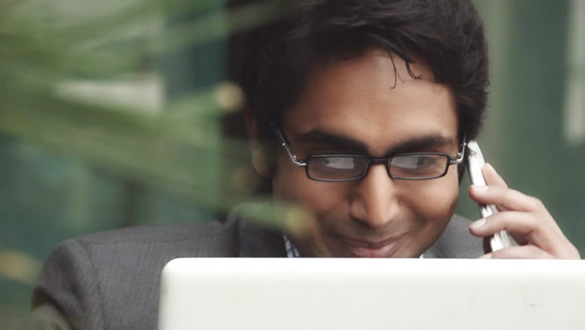 Shot of a businessman using a laptop while talking on mobile