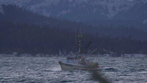 HOMER, AK - JANUARY 2013 - Frigid salt water spray splashes over the bow of a fishing boat in Kachemak Bay IN January 2013 near Homer, Alaska