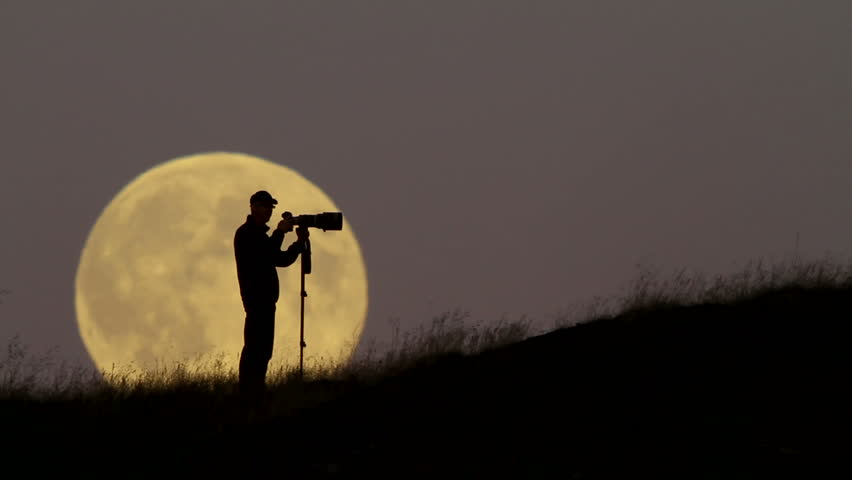 Man with a big camera, sihouetted against a rising full moon. | Shutterstock HD Video #4326653