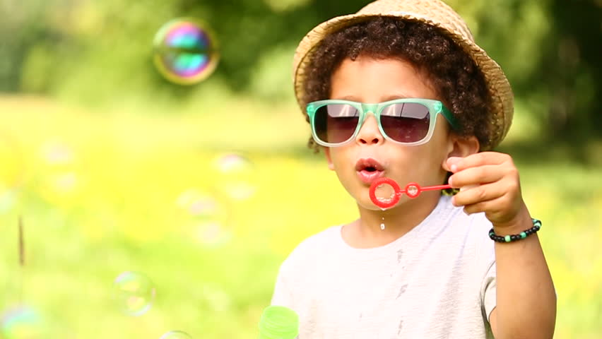 Young boy with hat and sunglasses playing in park
