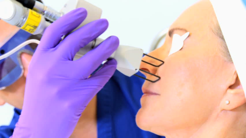 Close up male cosmetic surgeon performing non surgical facial treatments retired Caucasian female