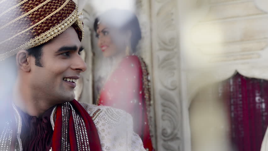 Shot of a Indian groom with bride standing in the background
