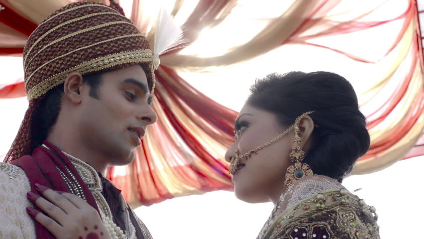 Shot of Indian bride and groom in traditional wedding dress talking to each other