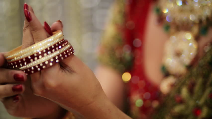 Shot of a Indian bride putting on bangles in her hand