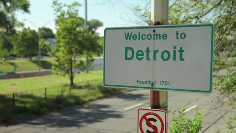 Welcome to Detroit sign by road. Detroit is the Motor City home of automotive manufacturing and a port city in an international border. Ford Motor, GM, Chrysler automation automotive