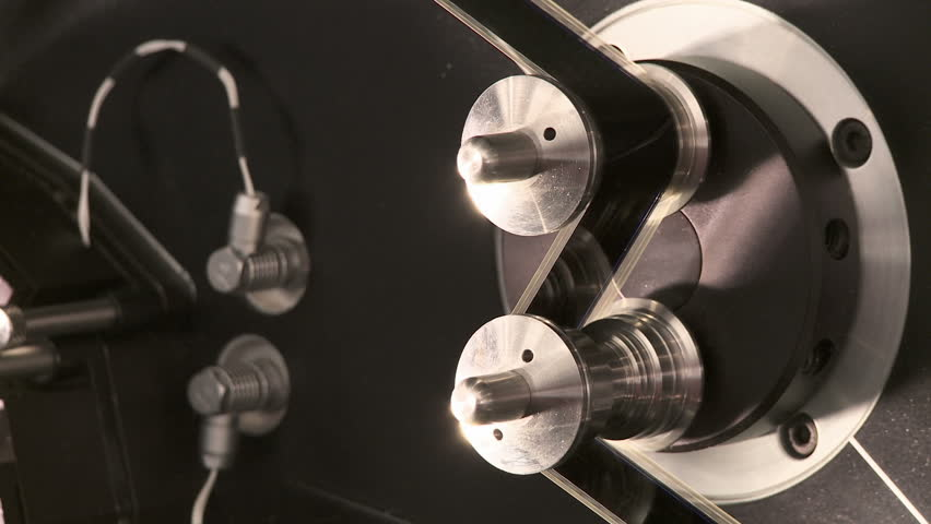 Detail of 35mm film moving continuously at 24fps around tension rollers in a