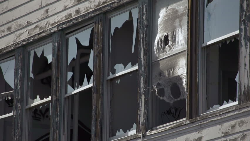 Abandoned building has broken windows ringed with shards of glass and ragged strips of burlap fluttering in the wind