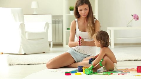 Charming babysitter and a little girl making colorful gouache handprints