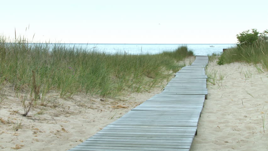 Early morning view along a boardwalk, past sand dunes, to Lake Michigan, USA.  Boat visible on the lake.