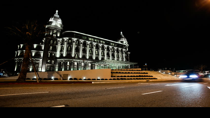 Time lapse of the new casino of Montevideo. Cars pass by at night. Low shutter speed - blurred lights and cars.