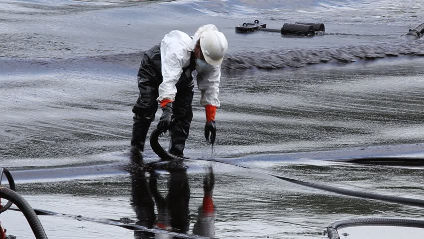 RAYONG, THAILAND - JULY 31, 2013: A worker in biohazard suit during the clean-up operation from crude oil spilled into Ao Prao Beach on July 31, 2013 in Rayong province, Thailand.