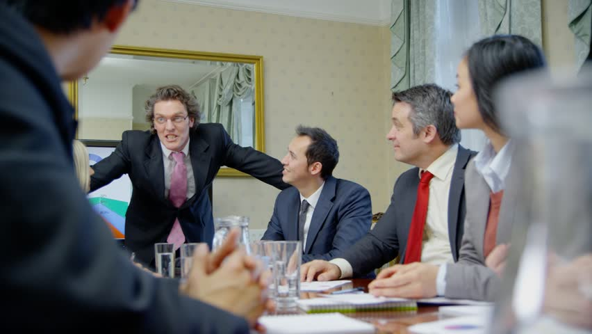 Happy and enthusiastic business team of mixed ages and ethnicity are seated around a conference table for a business meeting. They reach across the table to shakes hands with one another. Slow motion. | Shutterstock HD Video #4375133