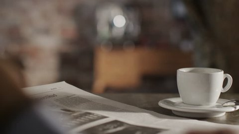 Man Reading Newspaper and Drink Coffee at Home. Shot on RED Digital Cinema Camera in 4K (ultra-high definition (UHD)), so you can easily crop, rotate and zoom, without losing quality!