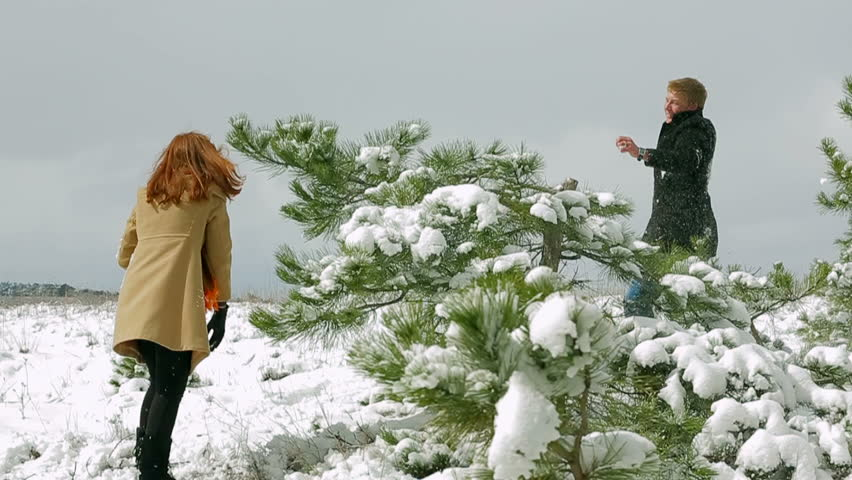 Man and woman playing snowballs in a forest.