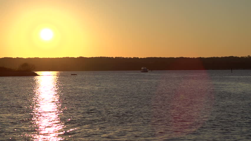 Sunset over water with ship