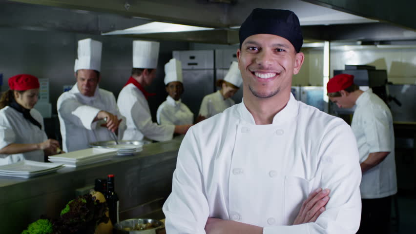 Portrait of a happy young trainee chef or worker in a commercial kitchen. The rest of the team of staff are working together, preparing food in the background. In slow motion.