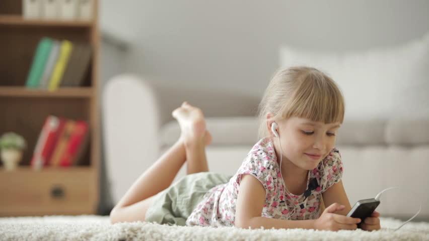 Funny Little Girl In Headphones Sitting On Carpet In -5129