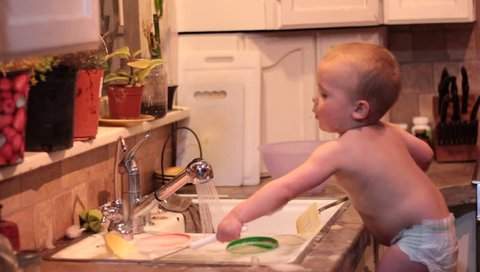 Little boy helping with the dishes but actually making a bigger mess of the kitchen.