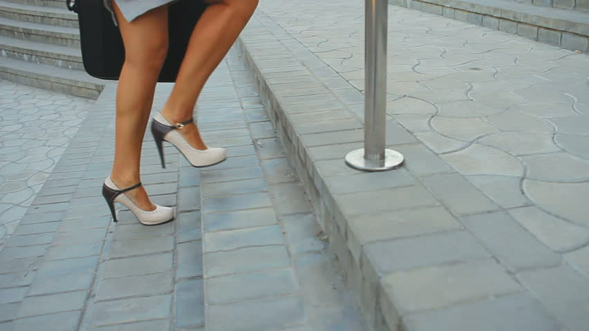Filmed feet only young business woman walking to the office and back. She climbs the stairs to the office building, and then back down. the camera moves following the movement of women.Odessa, Ukraine