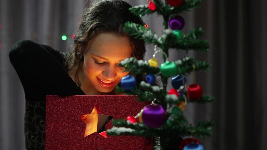 Girl at christmas tree getting a gift